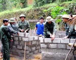 Lực lượng dân quân xã Đú Sáng (Kim Bôi) tích cực tham gia giúp đỡ các gia đình chính sách xây dựng hệ thống chuồng trại chăn nuôi hợp vệ sinh.