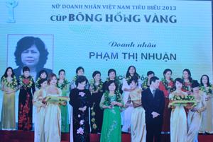 Bà Phạm Thị Nhuận (áo dài xanh đứng giữa, hàng đầu tiên) đón danh hiệu nữ doanh nhân Việt Nam nhận cúp Bông hồng vàng năm 2013.
