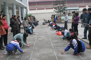 Các thí sinh tham gia thi vẽ tranh trên nền sân xi măng.
