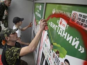 Người biểu tình phun sơn vào logo của ngân hàng Sberbank.
