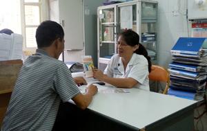 Anh Trương Quang Hưng trao đổi tài liệu tuyên truyền cùng bác sỹ Nguyễn Thị Thành tại phòng khám ngoại trú, khoa truyền nhiễm Bệnh viện Đa khoa tỉnh.