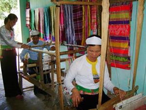 Nghệ nhân Bùi Thị Hạnh (người đứng) truyền dạy nghề dệt thổ cẩm  cho phụ nữ thôn Bãi Bệ 1, xã Dũng Phong (Cao Phong).