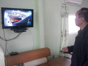 Đại tá Bùi Văn Minh  theo dõi quá trình chăm sóc lợn thịt qua hệ thống mạng.