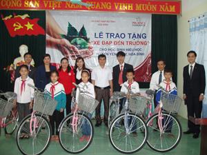 Đại diện công ty Prudential và Hội Chữ thập đỏ tỉnh trao xe đạp cho các em học sinh nghèo học sinh giỏi của huyện Yên Thủy.