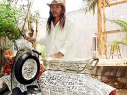 Nghệ sĩ Quang Đạt bên chiếc xe với 499 chữ ký