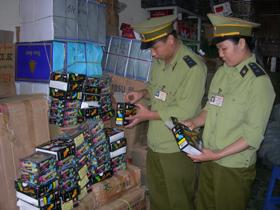 Cán bộ chi cục Quản lý thị trường tỉnh kiểm tra số kẹo mút phát quang vừa được thu giữ.