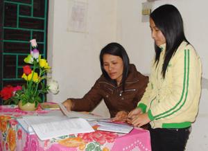 Em Hương đang trao đổi bài với cô giáo trong học tập.