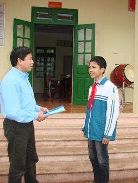 Em Ngô Thanh Tùng chia sẻ niềm vui về kết quả học tập với thầy Hiệu trưởng trường THCS Yên Lạc ( Yên Thuỷ).