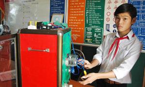 Học sinh lớp 9, Lê Minh Hiệu bên mô hình cỗ máy sấy lúa vừa đoạt giải