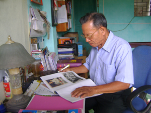 Ông Nguyễn Văn Sính và quyển album ảnh Bác do chính ông sưu tầm.