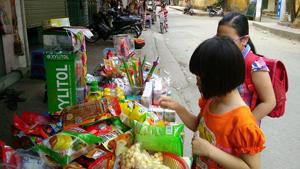 Học sinh trường tiểu học Lý Tự Trọng (TPHB) tranh thủ mua quà vặt ở cổng trường trước giờ vào lớp.