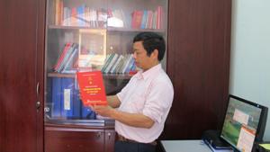 Đồng chí Bùi Văn Hợp, Phó trưởng Ban Tuyên giáo Huyện ủy Tân Lạc kiểm tra chất lượng in ấn công trình sưu tầm, biên soạn lịch sử Đảng của địa phương trước khi phát hành.