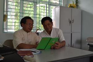 Ông Trần Ngọc Châu, Phó Chủ tịch Hội NCT thị trấn Mường Khến (bên trái) thường xuyên nghiên cứu các chế độ, chính sách của NCT qua sách, báo, tài liệu.