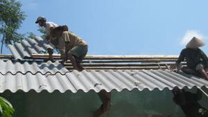 Các lực lượng được huy động giúp đỡ hộ bị thiên tai xã Do Nhân lợp lại mái nhà.