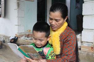 Chị Nguyễn Thị Đông tranh thủ lúc rảnh rỗi dạy cháu ngoại học bài.