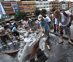 Người dân Thái Lan và khách nước ngoài (phải) tham gia rửa đường Rama IV ở Bangkok ngày 23.5.