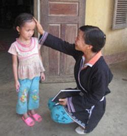 Y tế thôn bản Đặng Thị Mai đến trẻ em trong bản.