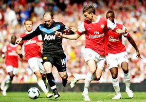 Tiền đạo Rooney (áo đen, Man.United) cố gắng đi bóng trước hàng phòng ngự Arsenal.