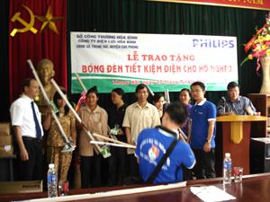 Đại diện Sở Công thương và Công ty Philips Việt Nam trao tặng bóng đèn tiết kiệm điện cho hộ nghèo xã Thung Nai (Cao Phong).