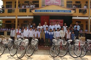 Đại diện Bộ LĐ-TB&XH trao xe đạp cho trẻ em nghèo vượt khó tại xã Mông Hóa (Kỳ Sơn).  Ảnh: Đ.P