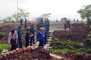 Lực lượng dân quân, ĐVTN và nhân dân giúp gia đình ông Đoàn Văn Phụng vận chuyển vật liệu, đào móng xây dựng nhà.