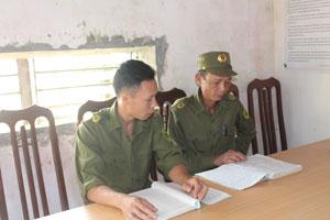 Anh Trần Thái Thành (bên trái) thường xuyên trao đổi kinh nghiệm tuyên truyền, vận động với công an viên các xóm, thôn.