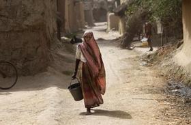 Một phụ nữ Ấn Độ xách xô đi lấy nước trong một ngày nắng nóng ở ngoại ô thành phố Amritsar, bang Punjab.