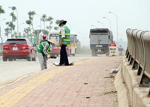 """Hai công nhân """"cần cù"""" thu dọn đất, cát, rác thải trên mặt đường đại lộ Thăng Long."""