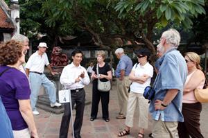 Hướng dẫn viên giới thiệu khu di tích Văn Miếu - Quốc Tử Giám với du khách nước ngoài. Ảnh: Linh Tâm