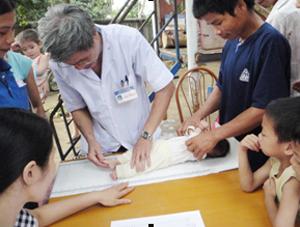 """Cán bộ trạm y tế xã Nhân Nghĩa đo cho trẻ trong  """"Ngày vi chất dinh dưỡng"""" năm 2011"""