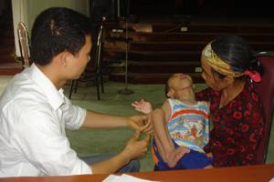 Bác sĩ Trung tâm Kỹ thuật chỉnh hình và Phục hồi chức năng Sơn Tây (Hà Nội) khám cho trẻ bị bại não huyện Lương Sơn.