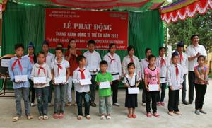 Đại diện Sở, ngành, huyện Kỳ Sơn trao quà cho học sinh nghèo đạt thành tích cao trong học tập.