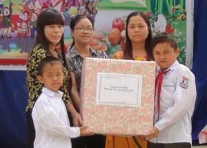 Đại diện huyện Tân Lạc tặng quà cho trẻ em xã Địch Giáo.