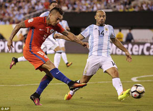 Tiền đạo Eduardo Vargas tung cú sút trước Javier Mascherano của Argentina.