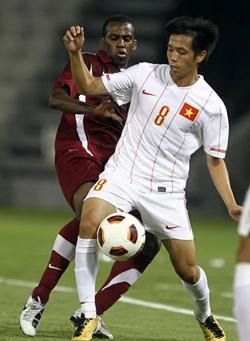Một pha bóng trong trận lượt đi giữa Việt Nam (áo trắng) và Qatar.