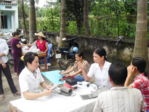 Cán bộ Trung tâm DS-KHHGĐ huyện khám bệnh, cấp thuốc miễn phí cho người dân xã Nhuận Trạch.
