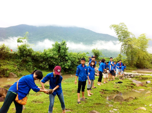 ĐVTN và sinh viên tình nguyện vận chuyển đá từ dòng suối xóm Vó Khang lên đắp đường giao thông.