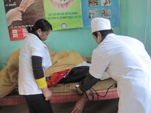 Cán bộ Trạm y tế xã Nuông Dăm (Kim Bôi) khám bệnh cho người dân có thẻ BHYT.