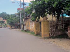 Cổng và nhà  làm việc (cũ) của Công ty môi trường đô thị TP Hòa Bình nằm sát mép đường An Dương Vương, ảnh hưởng đến mỹ quan đô thị và TTATGT.