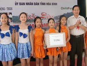 Đồng chí Bùi Văn Cửu, Phó Chủ tịch TT UBND tỉnh, Trưởng ban tổ chức, trao quà cho trẻ em tại diễn đàn.