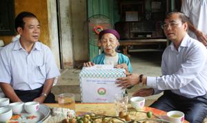 Thay mặt Tỉnh ủy, HĐND, UBND tỉnh, đồng chí Hoàng Văn Tứ, Phó Chủ tịch HĐND tỉnh trao quà cho bà mẹ VNAH Xa Thị Vân.