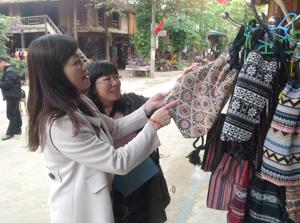 Khách du lịch thích thú lựa chọn mặt hàng thổ cẩm truyền thống - sản phẩm của người dân bản Lác, xã Chiềng Châu (Mai Châu).