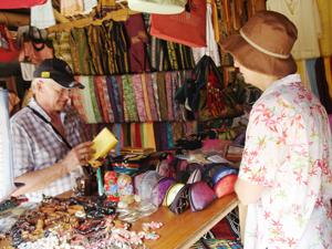 Du khách quốc tế chọn mua sản phẩm lưu niệm trong Khu du lịch cộng đồng bản Lác, xã Chiềng Châu (Mai Châu).