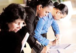 Người thất nghiệp đang điền đơn xin việc tại Hội chợ việc làm New York