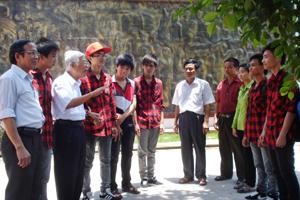 Thầy Nguyễn Bạch Đằng trò chuyện cùng lãnh đạo,  giáo viên, học sinh bên bức phù điêu truyền thống của nhà trường.