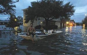 Một con phố bị ngập sâu ở Môn-tê-ô, bắc Ca-rô-li-na, khiến người dân phải dùng xuồng để di chuyển.