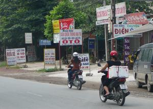 Bảng, biển quảng cáo đặt lộn xộn trên hành lang giao thông quốc lộ 6. ảnh chụp tại phố Ngọc, xã Trung Minh (TP Hòa Bình).