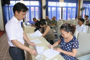 Cán bộ Phòng LĐ-TB&XH thành phố Hoà Bình hướng dẫn thân nhân NLĐ làm việc tại Hàn Quốc ký cam kết vận động người thân trở về nước đúng thời hạn hợp đồng lao động.