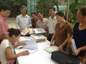 Cán bộ Phòng Bảo trợ xã hội (Sở LĐ-TB&XH) phát tài liệu cho các học viên tham gia lớp tập huấn.