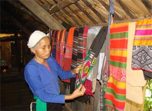 Bác Nguyễn Thị My, người lâu năm gắn bó với hoạt động du lịch đang giới thiệu với du khách các sản phẩm dệt thổ cẩm.